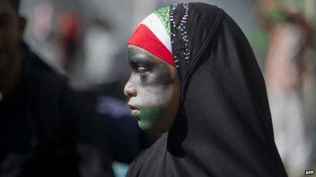 A girl wearing a hijab and with her face painted in the colours of the Palestinian flag takes part in a march in Cape Town on 9 August 2014