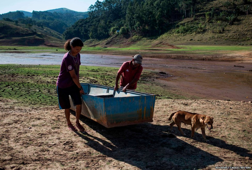 Residents drag a dinghy across the drying bottom of the Paraibuna dam in Brazil