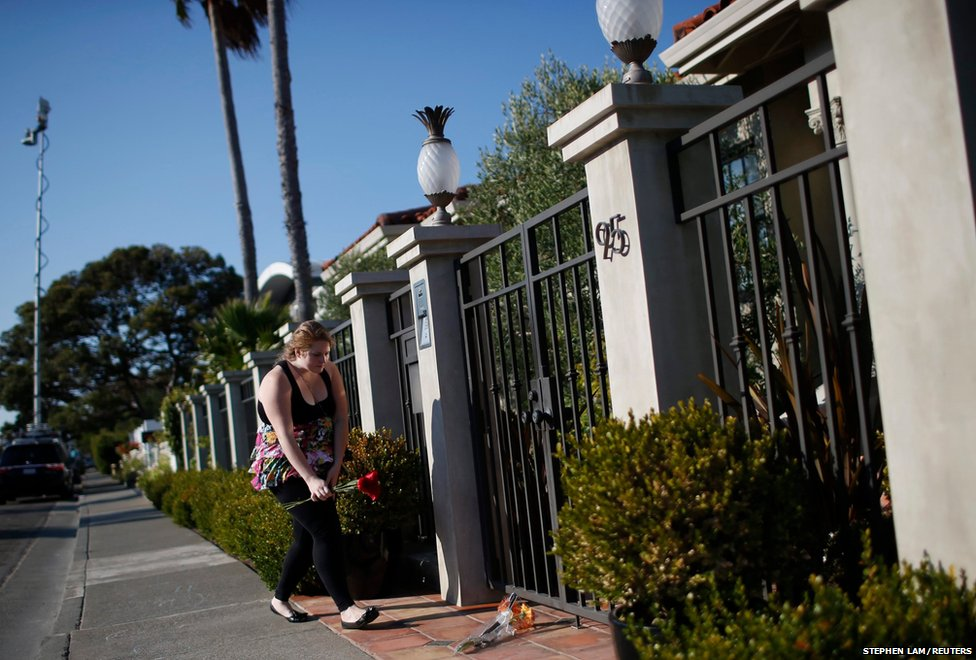 A woman leaves flowers outside the home of actor and comedian Robin Williams in Tiburon, California