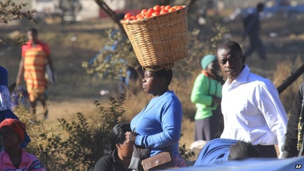 A women carries a basket with tomatoes in Mbare, Harare, 18 July 2014