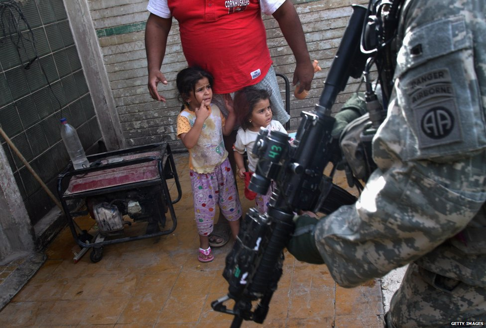Iraqi children look on as US troops inspect a neighbourhood during the 'surge'