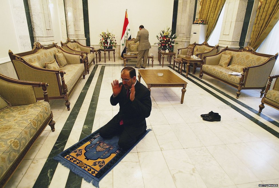 Mr Maliki prays in his office