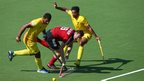 Owain Dolan-Gray is tackled during Wales' 3-1 defeat to India in the men's hockey at the Commonwealth Games.