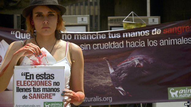 Protesters holds up a placard against bullfighting in Medellin during elections in February 2014