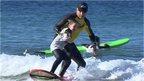 man teaching girl to surf