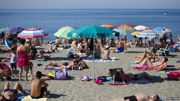 People sunbath at Ostia beach, west of Rome