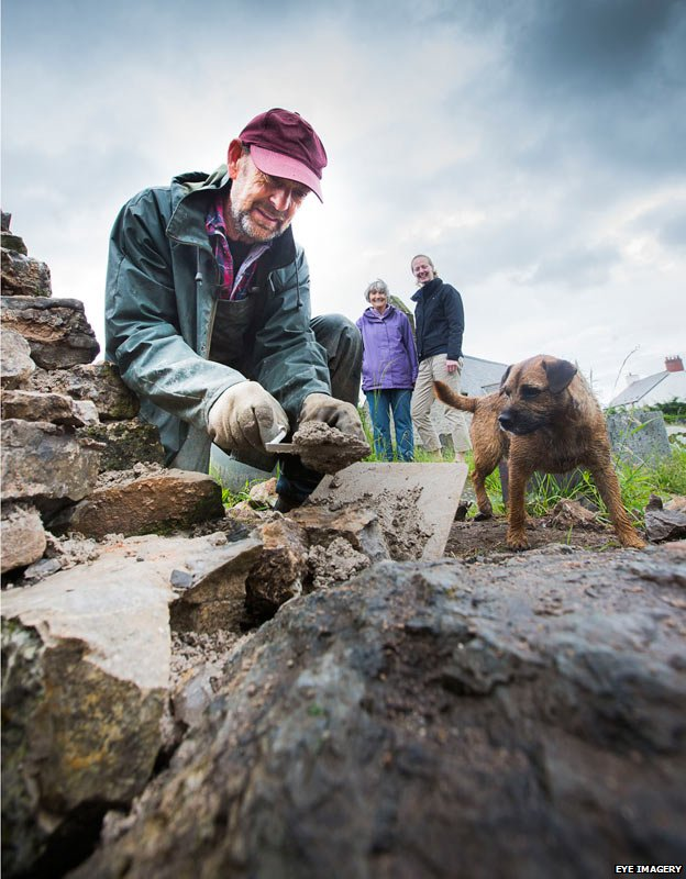 Stone waller Richard Jones is watched by Mws and church warden Yvonne McCormack and Sarah Jones, of Cadwyn Clwyd