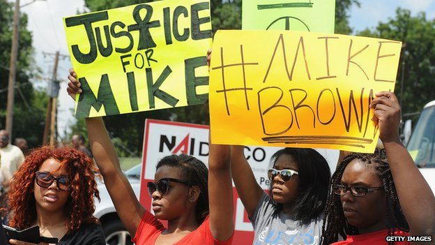 Protestors hold up signs calling for justice after the police shooting in Ferguson, Missouri.