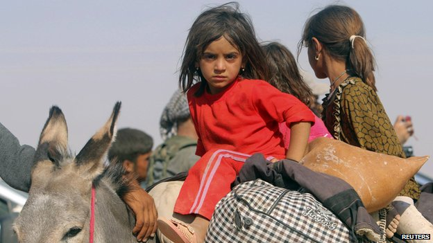 Displaced children from the minority Yazidi sect, fleeing violence from forces loyal to the Islamic State in Sinjar town, ride on a donkey as they head towards the Syrian border, on the outskirts of Sinjar mountain, near the Syrian border town of Elierbeh of Al-Hasakah Governorate August 11, 2014