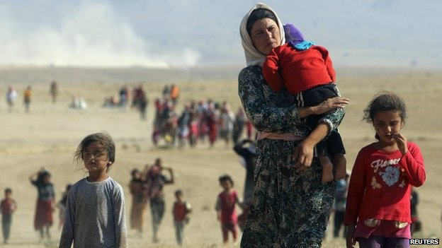 Displaced people from the minority Yazidi sect walk towards the Syrian border, on the outskirts of Sinjar mountain, near the Syrian border town of Elierbeh of Al-Hasakah Governorate, 12 August 2014