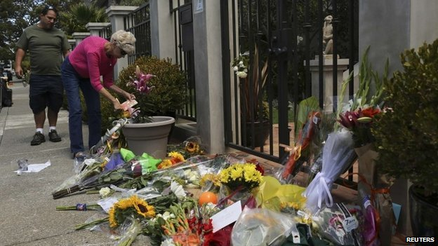 A woman places flowers and a card outside the home of actor Robin Williams in Tiburon, California 12 August 2014