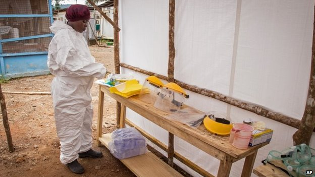 A healthcare worker prepares Ebola personal protective equipment before entering the Ebola isolation ward at Kenema Government Hospital, in Kenema, Sierra Leone, 12 August, 2014