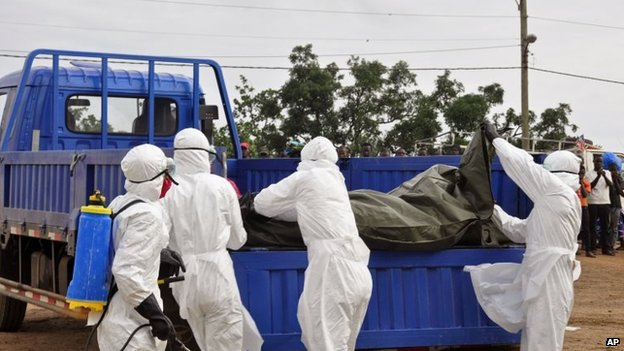 Health workers load the body of a man found on the street, suspected of dying from the Ebola virus, in the capital city of Monrovia, Liberia, 12 August, 2014