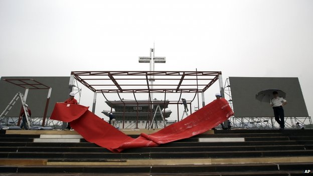 Workers lay a red carpet on the platform of a stage as they prepare for a special mass by Pope Francis at Gwanghwamun Square in Seoul, South Korea, on 13 August 2014