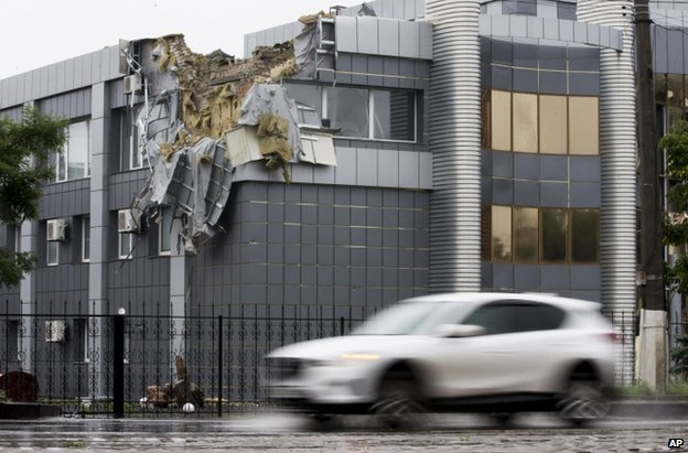 A car passes a shell-damaged building in Luhansk, east Ukraine (8 July 2014)