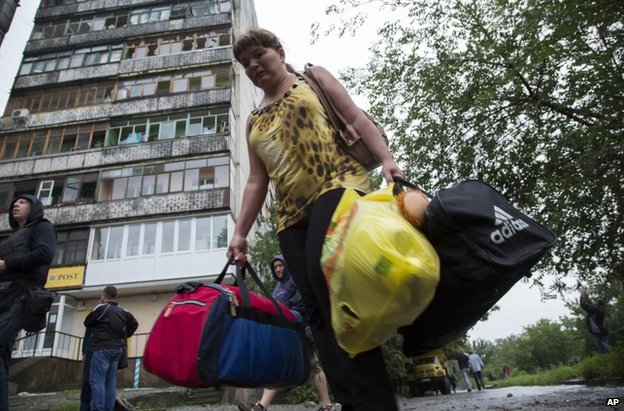 A woman leaves her shell-damaged block of flats in Luhansk, east Ukraine (8 July 2014)
