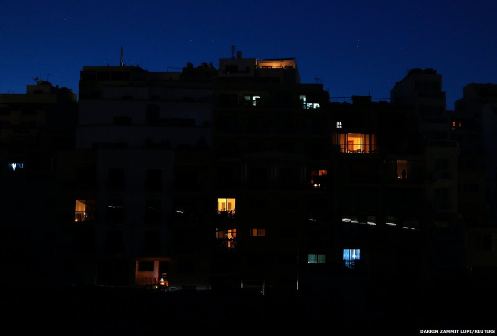 Residents use candles, torches and gas lamps during a nationwide power cut in St Julian's, outside Valletta