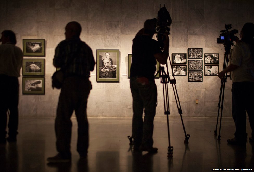 Journalists are seen at an exhibition, Fidel es Fidel in Havana