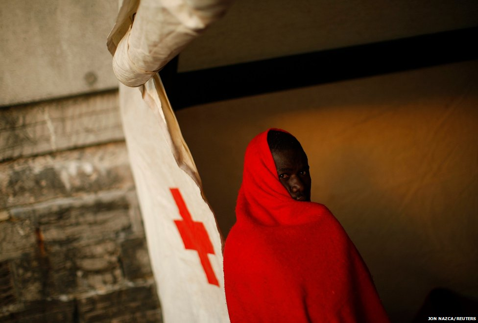An African immigrant wrapped in a blanket rests inside a Red Cross tent after arriving on a rescue ship at the southern Spanish port of Tarifa