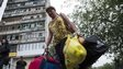 A woman leaves her shell-damaged block of flats in Luhansk, east Ukraine, 8 July