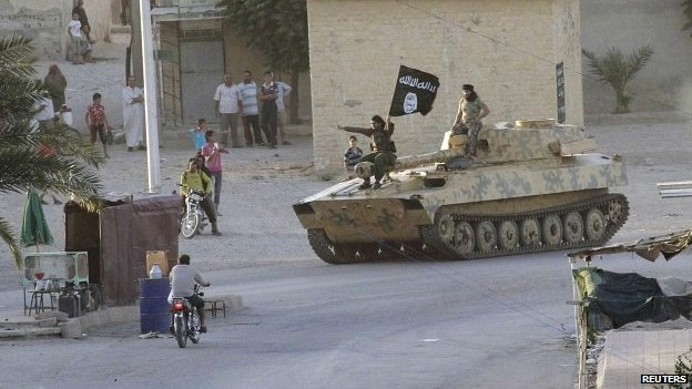 Residents watch Islamic State fighterson the streets of Syria's northern Raqqa province (30 June 2014)