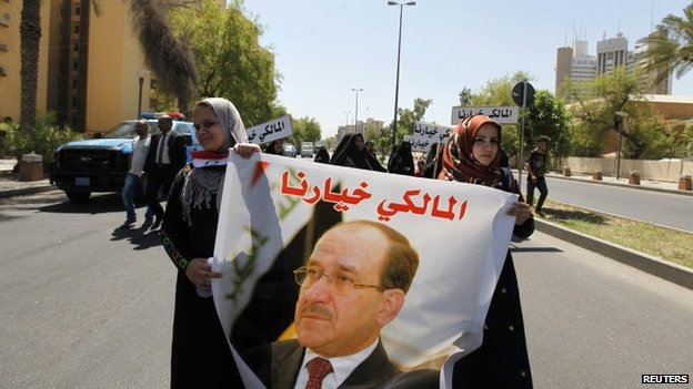 Iraqis carry portraits of incumbent Iraqi Prime Minister Nuri al-Maliki as they gather in support of him in Baghdad