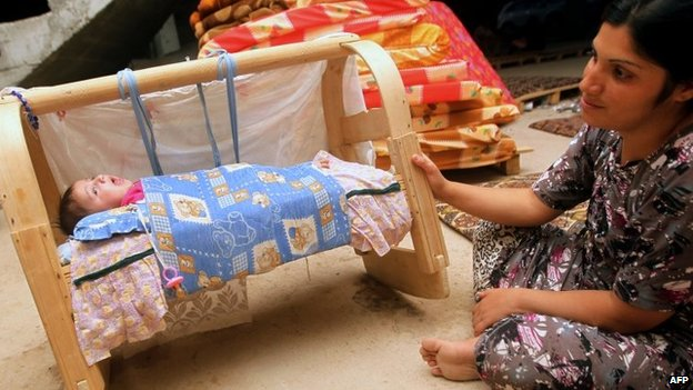 An Iraqi woman from the Yazidi community sits near her baby