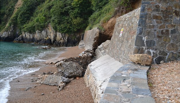 Breach in the Fermain Bay sea defences caused by storms in January and damaged suffered since