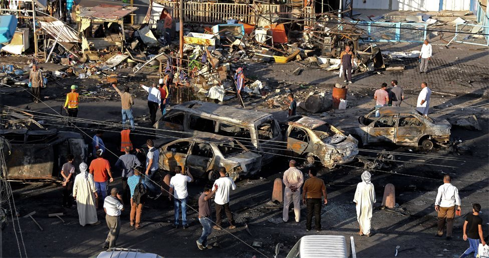 Iraqi civilians gather the morning after a string of car bombs tore through busy shopping streets in several neighborhoods in Baghdad, Iraq