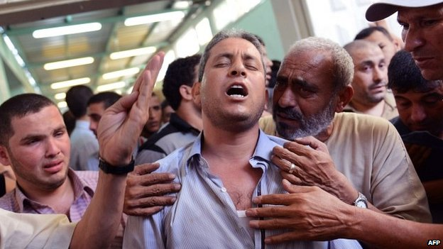 Palestinian man mourns death of a relative at Beit Lahiya mortuary 13/08/2014
