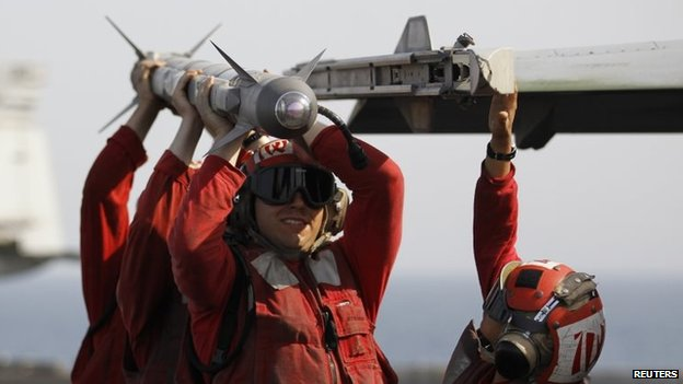 Weapon handlers carry an air to air missile on the aircraft carrier USS George H.W. Bush