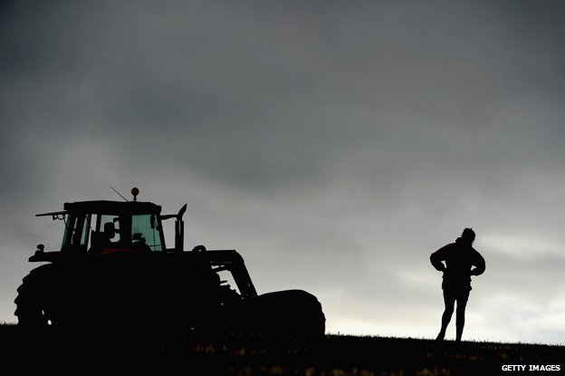 Scottish farmer silhouetted against horizon next to tractor