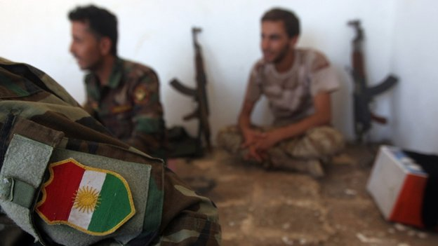 Peshmerga fighters rest with guns