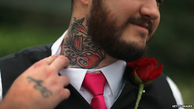 A man shows off his neck tattoo