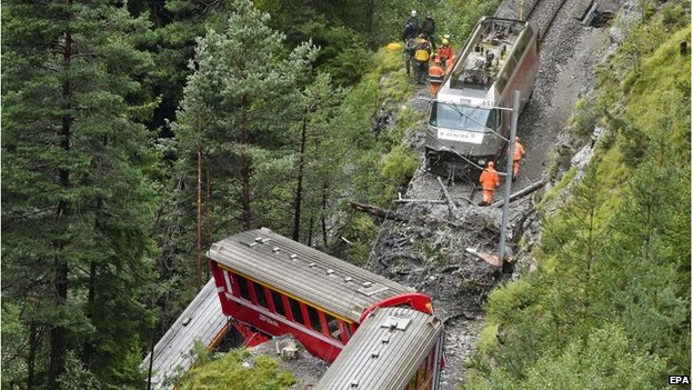 Rescuers work near a train after it was derailed by a landslide near Tiefencastel, in a mountainous part of eastern Switzerland, on August 13, 101