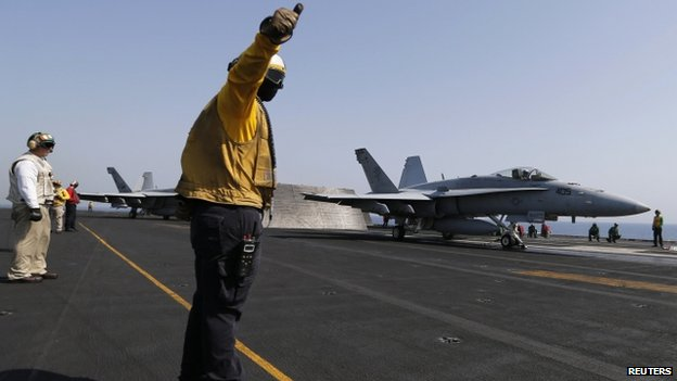 Flight deck crew member gives a thumbs up to take off to pilot of aircraft aboard USS George H W Bush (12 August 2014)
