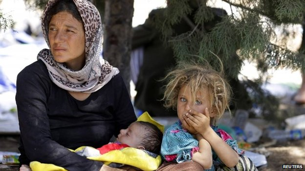 A displaced family from the minority Yazidi sect, fleeing the violence in the Iraqi town of Sinjar, waits for food while resting at the Iraqi-Syrian border crossing in Fishkhabour, Dohuk province, 13 August 2014