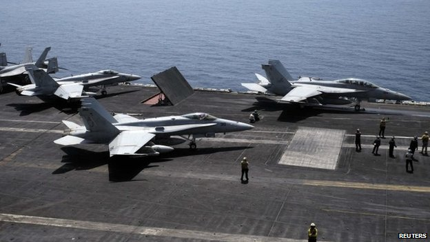 An F/A-18F Super Hornet of Strike Fighter Squadron (VFA-213) (R) and an F/A-18C Hornet of Strike Fighter Squadron (VFA-15) prepare for take off onboard the aircraft carrier USS George H.W. Bush in the Gulf, 13 August 2014