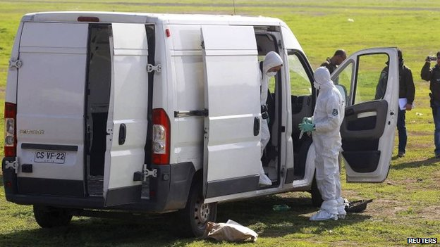 Chilean police inspect a vehicle which was used to in the robbery, August 12, 2014.