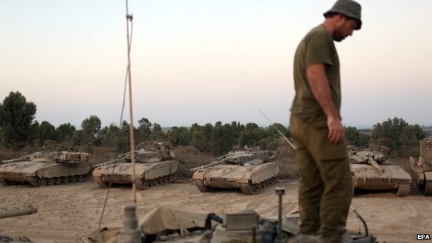 An Israeli reserve soldier on a Merkava tank at an unspecified location near the Israeli border with the Gaza Strip, 13 August 2014