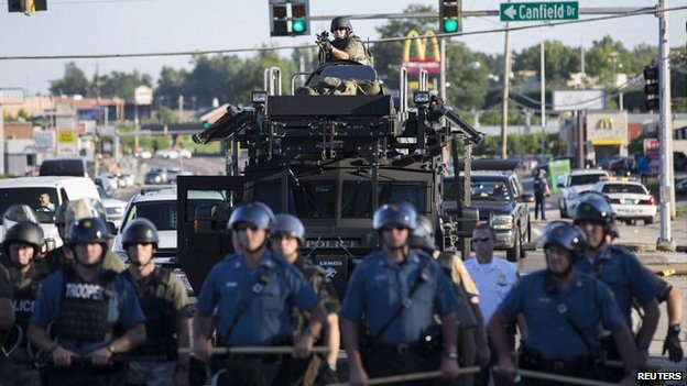 Riot police stand guard as demonstrators angry at the fatal shooting of Michael Brown gather in Ferguson, Missouri - 13 August 2014