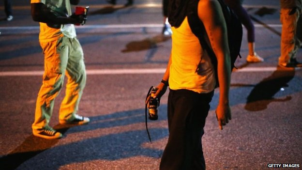 A young man carrying what appears to be a Molotov cocktail on the streets of Ferguson, Missouri - 13 August 2014
