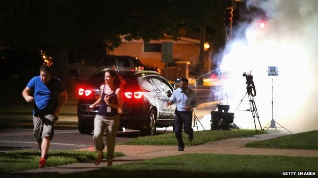 A TV camera crew run for cover to avoid tear gas fired close to their filming position - 13 August 2014