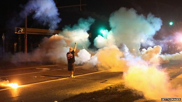 A demonstrator stands his ground amid tear gas fired by police during protests in Ferguson, Missouri - 13 August 2014