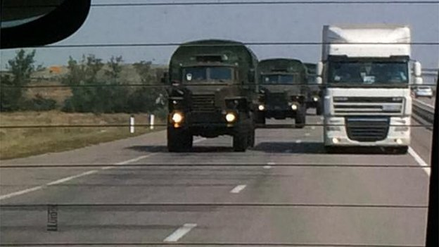 Military vehicles and white lorries in convoy en route to Rostov