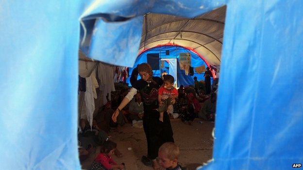 Displaced Iraqi Yazidis, who fled a jihadist onslaught on Sinjar, stand inside a tent after they took refuge at the Bajid Kandala camp in Dohuk province 13/08/2014