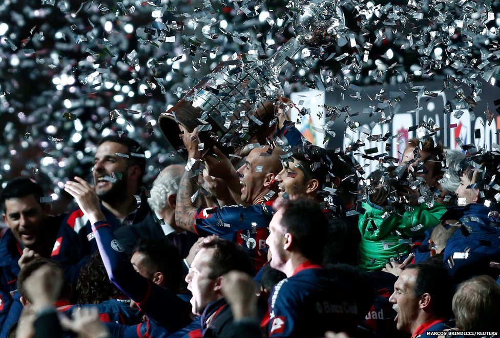 The footballers of Argentina's San Lorenzo celebrate with the trophy