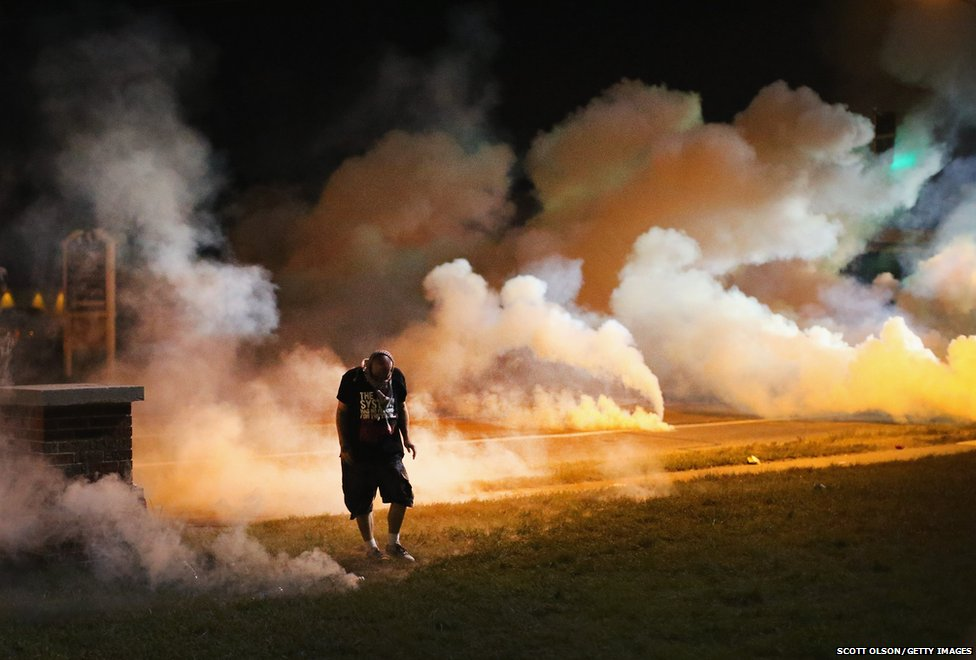 Demonstrators, protesting over the shooting death of teenager Michael Brown, flee as police shoot tear gas into the crowd