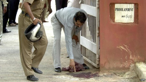 A police officer points to blood on the ground where Phoolan Devi was killed in front of her Delhi home (25 July 2001)