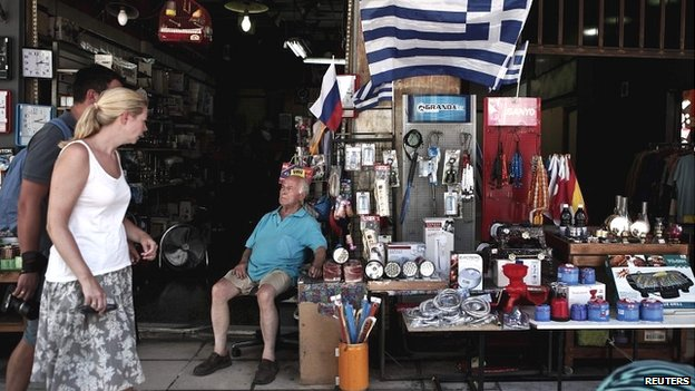 A shop owner looks at tourists walking by his shop in Athens - 13 August 2014